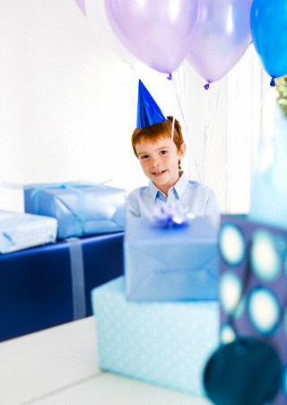 Boy at birthday party surrounded by presents